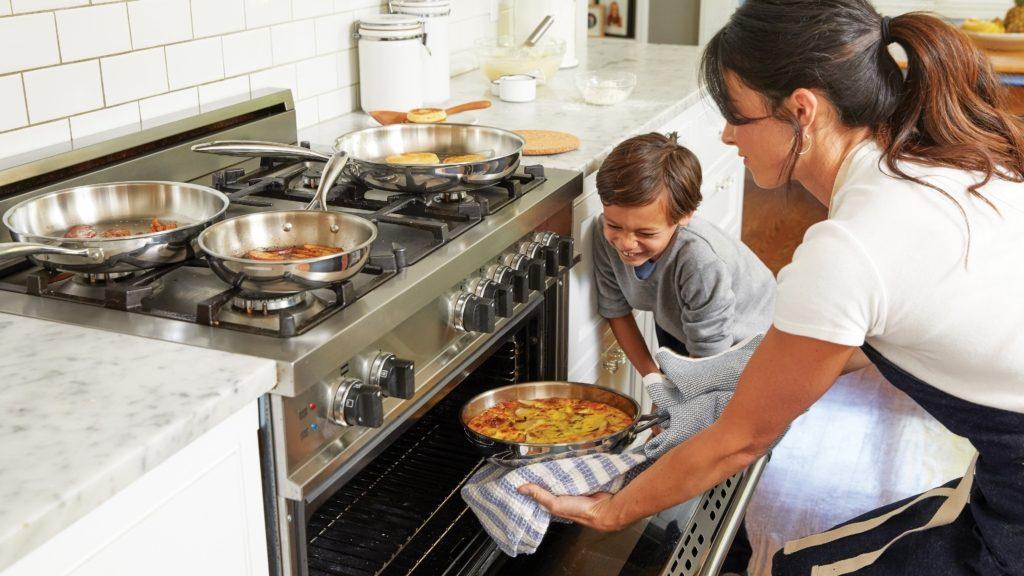 Femme avec un enfant qui sort une tarte d'un four