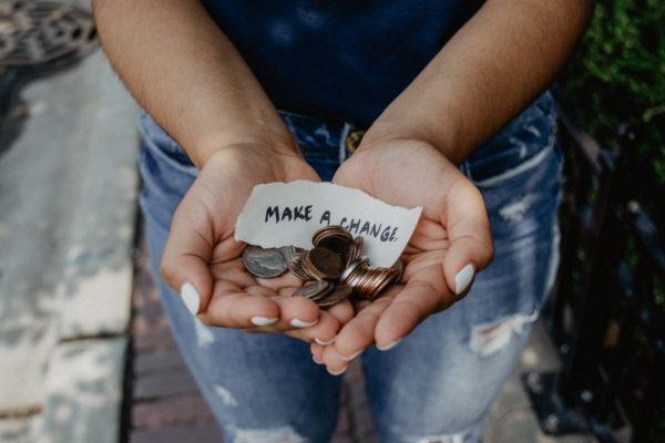 """Argent dans mains avec une écriture """"Make a change"""" sur un papier"""